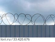 Купить «Barbed wire fixed with circles on a metallic solid light gray fence», фото № 33420676, снято 1 апреля 2020 г. (c) easy Fotostock / Фотобанк Лори