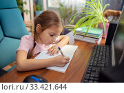 Girl schoolgirl does school homework at home in front of a computer. Стоковое фото, фотограф Екатерина Кузнецова / Фотобанк Лори