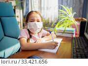 Купить «Girl schoolgirl in a medical mask does homework in front of a computer. Quarantine and home schooling», фото № 33421656, снято 2 июля 2020 г. (c) Екатерина Кузнецова / Фотобанк Лори