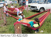 Купить «Дети отдыхают в гамаках рядом с автомобилями в туристическом кемпинге летом», фото № 33422020, снято 6 июля 2019 г. (c) Светлана Попова / Фотобанк Лори