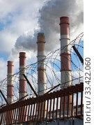 Купить «Factory chimneys smoke behind a fence with barbed wire», фото № 33422060, снято 22 марта 2020 г. (c) Алексей Кузнецов / Фотобанк Лори