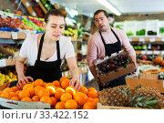 Купить «Female seller working with oranges», фото № 33422152, снято 27 апреля 2019 г. (c) Яков Филимонов / Фотобанк Лори
