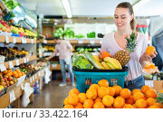 Young woman standing with full grocery cart during shopping in fruit shop. Стоковое фото, фотограф Яков Филимонов / Фотобанк Лори