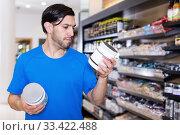 Купить «Serious young muscular sport man looking sport dietary supplements», фото № 33422488, снято 28 марта 2018 г. (c) Яков Филимонов / Фотобанк Лори