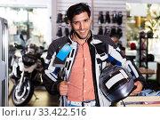 Купить «Man in moto equipment store», фото № 33422516, снято 1 сентября 2017 г. (c) Яков Филимонов / Фотобанк Лори