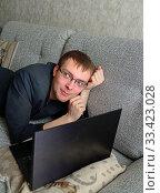 Купить «Dreamy young man working remotely on sofa at home during coronavirus pandemic», фото № 33423028, снято 21 марта 2020 г. (c) Валерия Попова / Фотобанк Лори