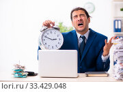 Купить «Young male employee unhappy with excessive work», фото № 33429048, снято 30 октября 2019 г. (c) Elnur / Фотобанк Лори