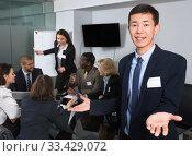 Купить «Successful business group with smiling Korean man foreground in», фото № 33429072, снято 12 февраля 2018 г. (c) Яков Филимонов / Фотобанк Лори
