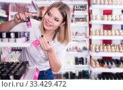 Купить «Young girl choosing color of nail polish», фото № 33429472, снято 31 января 2018 г. (c) Яков Филимонов / Фотобанк Лори