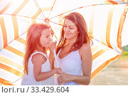 Купить «Mom with a small daughter walks along the beach with an umbrella on a sunny summer day.», фото № 33429604, снято 18 июля 2019 г. (c) Акиньшин Владимир / Фотобанк Лори