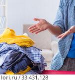 Купить «Young man husband doing clothing ironing at home», фото № 33431128, снято 19 декабря 2017 г. (c) Elnur / Фотобанк Лори