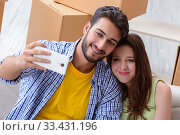 Купить «Young family unpacking at new house with boxes», фото № 33431196, снято 10 июля 2017 г. (c) Elnur / Фотобанк Лори