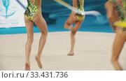 Купить «Young women teenagers in colorful swimsuits giving a performance at the rhythmic gymnastics tournament using colorful ribbons», видеоролик № 33431736, снято 27 мая 2020 г. (c) Константин Шишкин / Фотобанк Лори