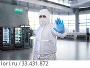 Купить «Epidemiologist in a protective suit shows a prohibition gesture against the waiting room at the airport or train station», фото № 33431872, снято 21 марта 2020 г. (c) Евгений Харитонов / Фотобанк Лори