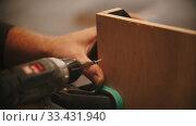 Купить «Carpentry working - man worker drills screws into the piece of plywood», видеоролик № 33431940, снято 2 июня 2020 г. (c) Константин Шишкин / Фотобанк Лори