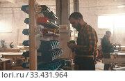 Купить «Carpentry industry - bearded man worker walking to the stand with different screws», видеоролик № 33431964, снято 2 июня 2020 г. (c) Константин Шишкин / Фотобанк Лори