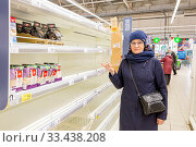 Russia, Samara, March 2020. Beautiful mature women are surprised at the empty shelves in the supermarket after rush demand during the epidemic. Text in Russian: millet. Редакционное фото, фотограф Акиньшин Владимир / Фотобанк Лори