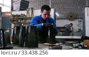 Concrete workshop - the master wiping the black concrete object with which he working. Стоковое видео, видеограф Константин Шишкин / Фотобанк Лори