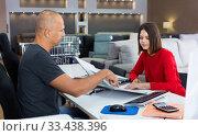 Купить «Female client consulting with shopper about choosing furniture in shop», фото № 33438396, снято 29 октября 2018 г. (c) Яков Филимонов / Фотобанк Лори
