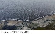 Купить «Aerial view, flying over coastline during a storm. Camera moves sideway to the right side above rocky shore and sea waves with foam», видеоролик № 33439484, снято 26 марта 2019 г. (c) Некрасов Андрей / Фотобанк Лори