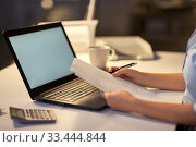 Купить «woman with laptop and papers at night office», фото № 33444844, снято 24 января 2019 г. (c) Syda Productions / Фотобанк Лори