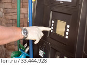 Купить «Method of protection against the virus. A hand in a disposable glove presses the buttons at a gas station», фото № 33444928, снято 25 марта 2020 г. (c) Ирина Кожемякина / Фотобанк Лори