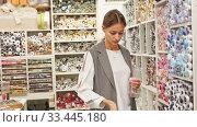 Купить «Skillful young seamstress looking for buttons for sewing clothes in haberdasher shop», видеоролик № 33445180, снято 3 апреля 2020 г. (c) Яков Филимонов / Фотобанк Лори