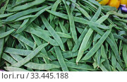 Купить «Closeup of fresh pods of green beans in plastic punnets on market counter», видеоролик № 33445188, снято 26 мая 2020 г. (c) Яков Филимонов / Фотобанк Лори