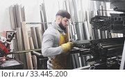 Купить «Young man worker with metal beams during work in workshop», видеоролик № 33445200, снято 29 марта 2020 г. (c) Яков Филимонов / Фотобанк Лори