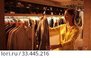 Купить «Young focused woman shopping casual clothes in modern men store», видеоролик № 33445216, снято 7 октября 2019 г. (c) Яков Филимонов / Фотобанк Лори
