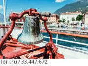 Купить «Bow of a boat with boat bell on a cruise tour. Blue water, mountain range and cute little village at Lago di Garda, Italy», фото № 33447672, снято 7 июля 2020 г. (c) easy Fotostock / Фотобанк Лори