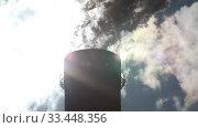 Купить «Factory Smokestack with thick smoke and steam in the bright rays of the sun», видеоролик № 33448356, снято 26 марта 2020 г. (c) Алексей Кузнецов / Фотобанк Лори
