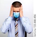 Купить «A business man in a mask grabbed his head with his hands», фото № 33448456, снято 26 марта 2020 г. (c) Владимир Арсентьев / Фотобанк Лори