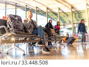 Casual blond young woman using her cell phone while waiting to board a plane at bussy airport departure gates. Стоковое фото, фотограф Matej Kastelic / Фотобанк Лори