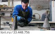 Concrete workshop - man is cleaning concrete pouring mold. Стоковое видео, видеограф Константин Шишкин / Фотобанк Лори