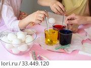 Купить «Дети мешают раствор с пищевым красителем в стаканах, для покраски пасхальных яиц», фото № 33449120, снято 28 марта 2020 г. (c) Иванов Алексей / Фотобанк Лори