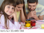 Купить «Семья ждет пока окрасятся яйца в стакане с красителями, девочка весело посмотрела в кадр», фото № 33449144, снято 28 марта 2020 г. (c) Иванов Алексей / Фотобанк Лори