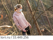 Купить «Corona virus, or Covid-19, is spreading all over the world. Portrait of caucasian sporty woman wearing a medical protection face mask while walking in the forest. Corona virus.», фото № 33449256, снято 28 марта 2020 г. (c) Matej Kastelic / Фотобанк Лори