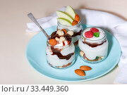 Купить «Sweet tasty milk curd creamy food in a glass jar of homemade breakfast. Cheesecake, English Trifle, Eton dessert, tiramisu, zuppa Inglese with nuts, almonds, cashews, hazelnuts, candied fruits and chocolate sauce», фото № 33449360, снято 14 декабря 2019 г. (c) Светлана Евграфова / Фотобанк Лори