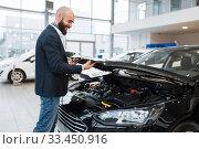 Купить «Man looking on transport engine in car dealership», фото № 33450916, снято 15 декабря 2019 г. (c) Tryapitsyn Sergiy / Фотобанк Лори