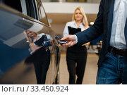 Купить «Man and saleswoman choosing auto in car dealership», фото № 33450924, снято 15 декабря 2019 г. (c) Tryapitsyn Sergiy / Фотобанк Лори