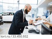 Купить «Man signs a contract in car dealership», фото № 33450932, снято 15 декабря 2019 г. (c) Tryapitsyn Sergiy / Фотобанк Лори
