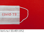 Medical disposable face mask on a red background with the inscription Kovid 19. World pandemic coronavirus. Stop the pandemic. Health and prevention of influenza and an infectious outbreak. Quarantine. New 2019 nCoV virus. Стоковое фото, фотограф Tetiana Chugunova / Фотобанк Лори