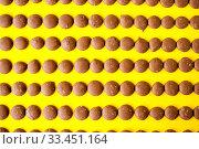 Купить «Drops of milk chocolate are laid out in a row on a yellow background», фото № 33451164, снято 14 марта 2020 г. (c) Катерина Белякина / Фотобанк Лори