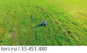 Купить «Low orbital flight around man on green grass with notebook pad at yellow rural field.», видеоролик № 33451480, снято 13 марта 2019 г. (c) Александр Маркин / Фотобанк Лори