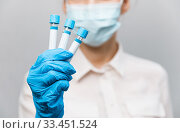 Купить «Girl Doctor in medical mask and rubber gloves, holds in her hands, closeup of test tube with tests for the presence of covid-19. Doctor in medical clothes demonstrates test tubes with coronavirus», фото № 33451524, снято 22 марта 2020 г. (c) Сергей Тимофеев / Фотобанк Лори