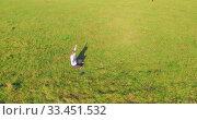 Купить «Low orbital flight around man on green grass with notebook pad at yellow rural field.», видеоролик № 33451532, снято 18 марта 2019 г. (c) Александр Маркин / Фотобанк Лори