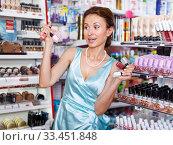 Купить «Woman holding nail polishes in cosmetics shop», фото № 33451848, снято 21 июня 2018 г. (c) Яков Филимонов / Фотобанк Лори