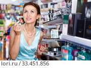 Купить «Stylish woman testing new lipstick, shopping in cosmetics store», фото № 33451856, снято 21 июня 2018 г. (c) Яков Филимонов / Фотобанк Лори