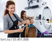 Купить «Hairdresser cutting hair of female client», фото № 33451888, снято 26 июня 2018 г. (c) Яков Филимонов / Фотобанк Лори